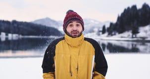 Ung karismatisk grabbstående som ser rak till den stora kameran och le honom för att få skjuta vid en snöboll i ett perfekt lager videofilmer