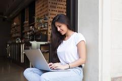 Ung keyboarding för kvinnlig student på hennes bärbar datordator, medan sitta i restaurang i den nya luften i sommardag Arkivfoto