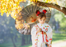 Ung kimonoflicka med det traditionella paraplyet Fotografering för Bildbyråer