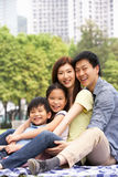 Ung kinesisk familj som tillsammans kopplar av i Park Royaltyfri Fotografi