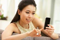 Ung kinesisk kvinna som hemma använder den mobila telefonen Royaltyfri Foto