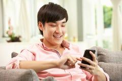 Ung kinesisk man som använder den mobila telefonen Arkivfoto
