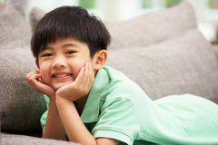 Ung kinesisk pojke som hemma kopplar av på sofaen Arkivfoton