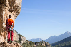 Ung klättrare som hänger vid en klippa Arkivfoto