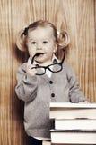 Ung klyftig flicka med böcker och exponeringsglas Royaltyfri Fotografi