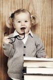 Ung klyftig flicka med böcker och exponeringsglas Royaltyfri Bild