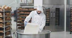 Ung kockbagare med ett skägg som förbereder degen att tillfoga något mer mjöl i en stor behållare, tagande för bakgrundsbageriarb stock video