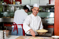 Ung kockdanandepizza på kök royaltyfri fotografi