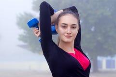 Ung konditionflicka som övar med dumbells under utbildningsarbete Royaltyfria Foton