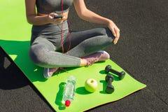 Ung konditionidrottskvinna som sitter och använder smartphonen i idrottshall Flicka på yoga som är matt med botte av vatten, hant royaltyfria bilder