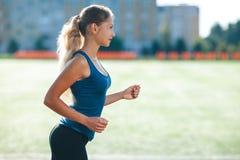 Ung konditionkvinna i en blå skjorta och damasker som kör på ett stadionspår Idrottsman nenflicka som gör övningar på utbildninge arkivbilder
