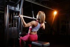 Ung konditionkvinna som gör övningar som den viktiga muskeln grupperar i idrottshallen Styrkautbildning Fotografering för Bildbyråer