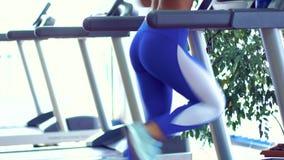 Ung konditionkvinna som gör cardio övningar på idrottshallspringen på en trampkvarn stock video