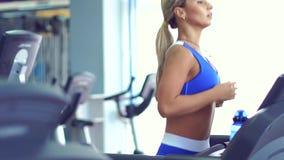 Ung konditionkvinna som gör cardio övningar på idrottshallspringen på en trampkvarn lager videofilmer