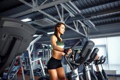Ung konditionkvinna som gör cardio övningar på idrottshallspringen på en trampkvarn Arkivbild