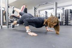 Ung konditionkvinna som utarbetar g?ra skjuta-UPS p? golv i sportidrottshall Sport, kondition, utbildning, livsstil och folkbegre arkivbild