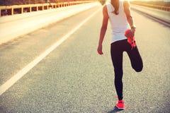 Ung konditionkvinnalöpare som sträcker ben Arkivbilder