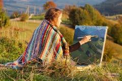 Ung konstnär som målar ett höstlandskap Royaltyfri Foto