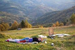 Ung konstnär som sovar i en äng Arkivfoton