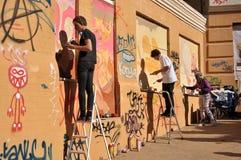 Ung konstnärmålarfärg väggen arkivbilder