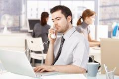 Ung kontorsarbetare som använder bärbara datorn som talar på telefonen arkivfoto