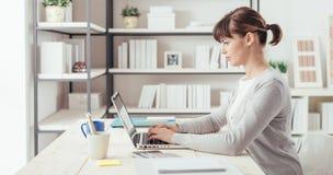 Ung kontorsarbetare som arbetar på skrivbordet arkivfoto