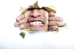 Ung koreansk man som ser till och med det rev sönder pappers- hålet Arkivbild