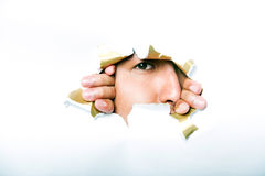 Ung koreansk man som ser till och med det rev sönder pappers- hålet Arkivbilder
