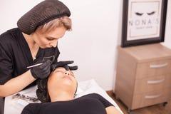 Ung kosmetolog som använder needls för ögonbryntatueringborttagning i hennes klinik arkivfoton