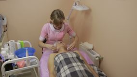 Ung kosmetolog som gör framsidalokalvårdtillvägagångssätt arkivfilmer