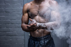 Ung kroppsbyggare som skakar krita av hans händer Arkivbild
