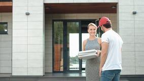 Ung kurir som levererar pizza till det lyxiga huset Le kvinnan som tar pizzaaskar stock video
