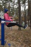 Ung kvinna, övning på en sportsimilator, natur, höst, livsstil, skog royaltyfria foton