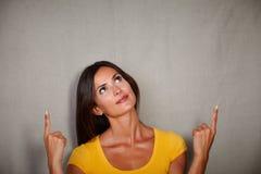 Ung kvinna av caucasian etnicitet som pekar upp Royaltyfri Fotografi