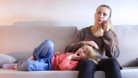 Ung kvinna av europeiskt utseendemässigt sammanträde på soffan och samtal på telefonen arkivfilmer