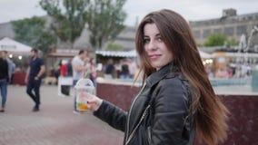 Ung kvinna av långt hår, gladlynt flicka med coctailen i mittstaden, attraktiv kvinnabrunett utomhus, lycklig kvinnlig arkivfilmer