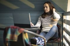 Ung kvinna, bärbar dator, balkong, kopp te, natur arkivfoto