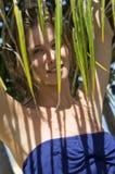 Ung kvinna bak en palmträd Royaltyfria Foton