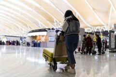 Ung kvinna bakifr?n som transporterar bagage fr?n ankomstparkering till avvikelseterminalen f?r internationell flygplats med baga arkivbilder