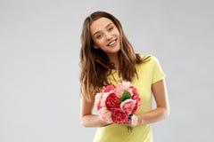 Ung kvinna eller ton?rs- flicka med blommabuketten arkivbilder