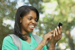 Ung kvinna för afrikansk amerikan på den smart telefonen Fotografering för Bildbyråer