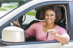 Ung kvinna för afrikansk amerikanflicka som kör bilinnehavtangent Arkivbild