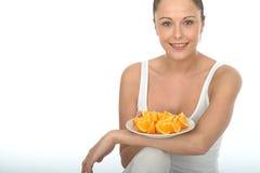 Ung kvinna för attraktiv lycklig sund passform som rymmer en platta av mogna orange segment Arkivfoton
