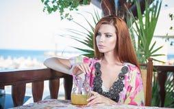 Ung kvinna för attraktivt rött hår med den ljusa kulöra blusen som dricker lemonad på en terrass som har det blåa havet i bakgrun Arkivfoton
