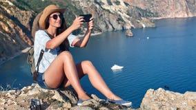 Ung kvinna för attraktivt stilfullt lopp som tar selfie genom att använda smartphonen som överst poserar av berget stock video