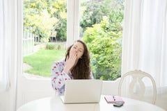 Ung kvinna för avgasrör som framme sitter av bärbara datorn Fotografering för Bildbyråer