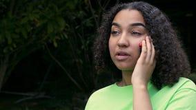 Ung kvinna för Biracial afrikansk amerikanflickatonåring som bär en grön t-skjorta som talar på en mobil mobiltelefon stock video