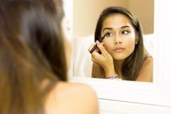 Ung kvinna för blandat lopp med borsteögoneyeliner på att se i mien royaltyfri bild