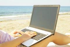 Ung kvinna för blont hår som arbetar på bärbara datorn på stranden på solig dag Slutet av kvinnlign räcker upp maskinskrivning på arkivfoto