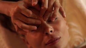 Ung kvinna för framsida som får hudmassage i skönhetbrunnsortsalong Slut upp den härliga kvinnan som mottar framsidamassage i skö lager videofilmer